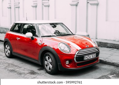 Vilnius, Lithuania - July 7, 2016: Red Color Car With White Stripes Mini Cooper Parked On Street In Old Part European Town. All colors except red are reduced