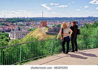 Vilnius, Lithuania - June 13, 2016: Women taking photo of Gediminas Tower on the hill and the Lower Castle down the hill in Vilnius in Lithuania. The Tower is also called Upper Castle