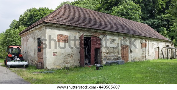 VILNIUS, LITHUANIA - JUNE 17, 2016: Rustic shed and garage for tractor in the Botanical Garden of Vilnius University. At the beginning of the 18th century it was the stable of the governor of Vilnius