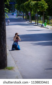 Vilnius / Lithuania - June 28 2015: Pretty female photographer taking photos of the bicycle race on a street.