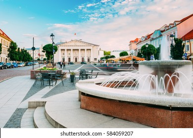 Vilnius, Lithuania. The Marble Fountain And View Of Didzioji Street, The Ancient Place In Old Town In Summer Day Under Blue Sky.