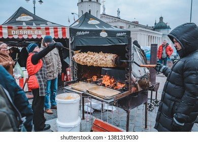 "Vilnius, Lithuania - March 3, 2019: The celebration of the big lithuanian fair ""Kaziuko Muge"". Process of preparation of big Lithuanian Tree Cake, known as Raguolis or Sakotis."