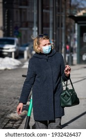 Vilnius, Lithuania - March 9 2021: Woman or lady wearing mask walking in the city near a shop or shopping center during Covid or Coronavirus outbreak, vertical