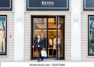 VILNIUS, LITHUANIA - MAY 03, 2016: Businessman leaving Hugo Boss luxury fashion house store  in Vilnius, Lithuania