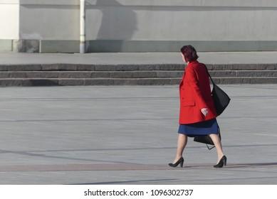 Vilnius, Lithuania - May 08, 2018: Woman in red coat walkin