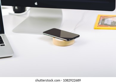 VILNIUS, LITHUANIA - MAY 10, 2018: iPhone X smart phone and wireless charger on working table. Latest Apple Iphone 10 mobile phone. Future technology concept.