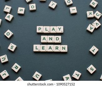 Vilnius, Lithuania, May 14, 2018: PLAY AND LEARN words made from Scrabble game tiles on green background. Education and learning concept.