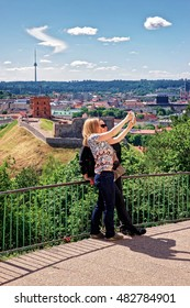 Vilnius, Lithuania - May 26, 2016: Women making selfie with Gediminas Tower on the hill and the Lower Castle down the hill in Vilnius in Lithuania. The Tower is also called as Upper Castle.