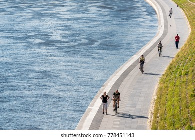 VILNIUS, LITHUANIA - May 29 2017. People walking and riding bicycles near river Neris in Vilnius city center.