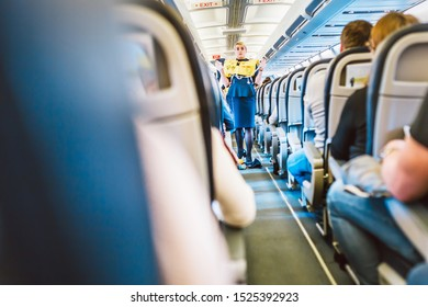 Vilnius, Lithuania - October 01, 2019: In the cabin of an AirBaltic aircraft, the flight attendant demonstrates safety rules and a life jacket before flight