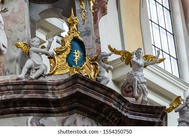 Vilnius, Lithuania - October 26, 2019: Detail of one of the Rococo altars of the Dominican Church of the Holy Spirit in Vilnius.The cross and the cereal sheaf in a cartouche surrounded by white angels
