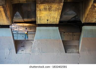 Vilnius, Lithuania - September 22, 2020:  Skater girl looks at smart phone under the pylons of a bridge across Neris river in Vilnius.