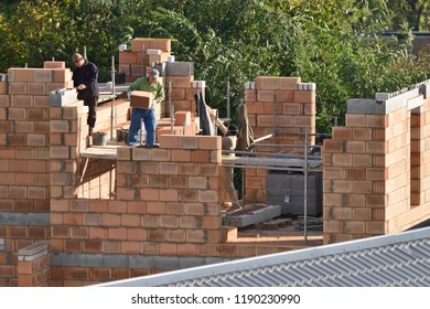 Vilnius, Lithuania - September 27: Unidentified bricklayers, industrial workers installing brick masonry on exterior wall on September 27, 2018 in Vilnius Lithuania.