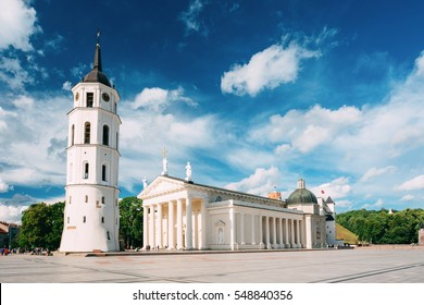 Vilnius, Lithuania. View Of Bell Tower And Facade Of Cathedral Basilica Of St. Stanislaus And St. Vladislav On Cathedral Square, Famous Landmark, Showplace In Sunny Summer Under Blue Sky With Clouds.