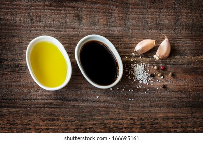Vinaigrette or french dressing recipe ingredients on vintage wood background. Olive oil, balsamic vinegar, garlic, salt and pepper from above.