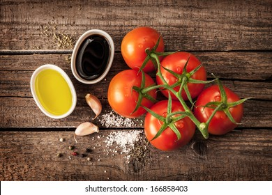 Vinaigrette or french dressing recipe ingredients and tomato branch on vintage wood background. Olive oil, balsamic vinegar, garlic, salt and pepper from above.