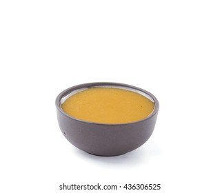 Vinaigrette sauce in brown bowl isolated on white background. Closeup.