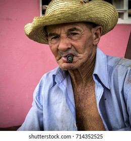 VINALES - AUGUST 22: An old tobacco farmer enjoys a cigar during a lunch break at his farmhouse in Vinales, on August 22, 2017 in Vinales, Cuba.