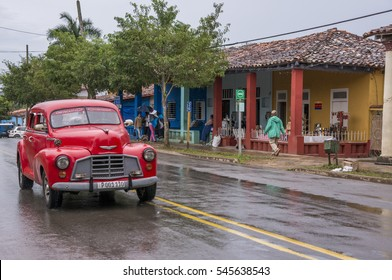 VINALES, CUBA - JANUARY 21, 2016: Old red american classic car, circling the main street after the rain