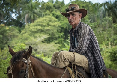 VINALES, CUBA - JUNE 19, 2017: A farm worker rests on his horse after a day of work in the tobacco plantations of Vinales in Cuba.  The Vinales region is famous as a leading producer of fine cigars.
