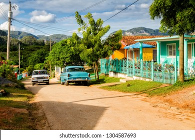 VINALES, CUBA - NOV 18, 2017: Old fashioned vintage car on a rural road by the summer colorful house in the town of Vinales, Cuba