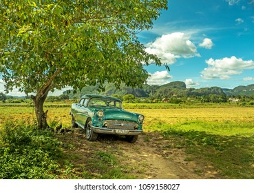 Vinales, Cuba - November 2018 - Buick Old-Timer Taxi in shade underneath tree with green hills and a blue clouded sky