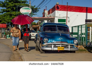 VINALES - FEBRUARY 4: Two women with an umbrella walk near a classic car parked on the street on February 4, 2013 in Vinales. In Cuba umbrella is very often used as a protection from Sun.