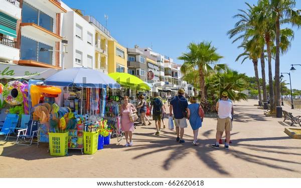 VINAROS, SPAIN - JUNE 12, 2017: People walking in the Paseo Blasco Ibanez promenade in Vinaros, Spain, the seaside promenade next to the Playa del Forti beach