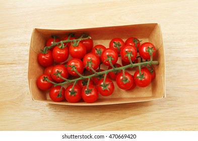 Vine ripened tomatoes in a cardboard carton on a wooden board