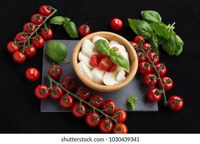 Vine tomatoes, sliced mozzarella and fresh basil on a black background