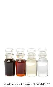 Vinegar, balsamic vinegar, maple vinegar and apple vinegar in glass vial over white background