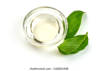 Vinegar in glass bowl with basil leaves, isolated on white background.