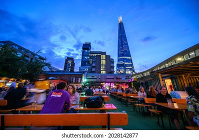 Vinegar Yard, London, UK - Aug 11 2021: Vinegar Yard is an open air bar near London Bridge. Customers enjoy a drink at the outdoor seating just after sunset. The Shard and Guy's Hospital are behind.