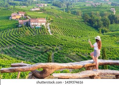 Vineyard Prosecco on the green hills near Valdobbiadene, girl with a glass of Prosecco wine, Veneto, Italy