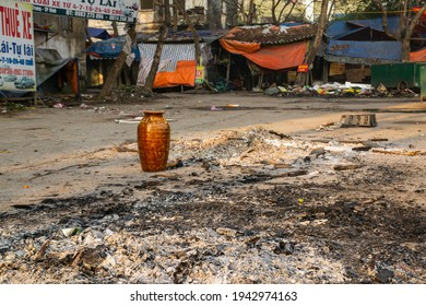Vinh city, Vietnam -  Feb. 12 2021: The scene after campfire party for lunar new year in Vietnam, an empty jar  of  fermented rice wine (Can wine) and ash heap.