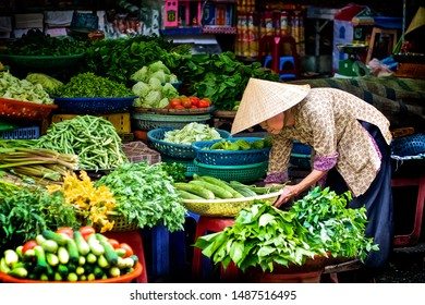 VINH LONG, CAN THO / VIETNAM - Apr 9,2011: Old woman with vegetables stall in traditional market.