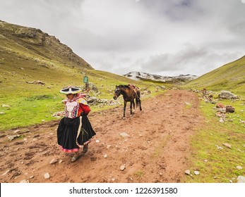 Vinicunca, Peru - January 7, 2017. View of a woman carrying a horse used for tourist transportation in the Vinicuca mountain.