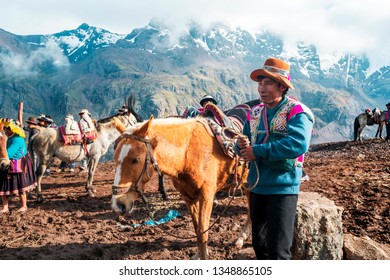 VINICUNCA, PERU- OCTOBER 29: mountain guide in traditional wear holds red mule at high altitude grounds in Vinicunca, Peru on October 29, 2019