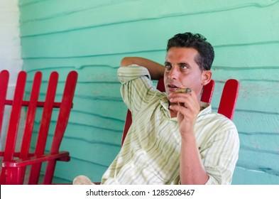 Vinjales / Cuba - June 9 2014: Tobacco farmer sits on the rocking chair smoking cigar in Vinjales, Cuba.