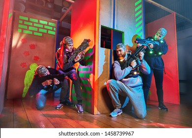 Vinnitsa, Ukraine - 22 December , 2018:  Group of young people having fun on dark lasertag arena in colorful beams of laser guns