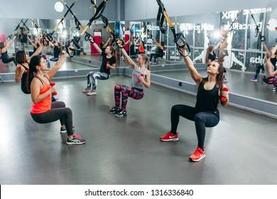 VINNITSA, UKRAINE - January 10, 2019: Women training with trx fitness straps