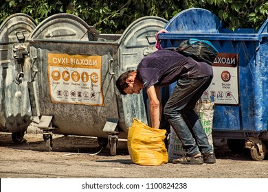 Vinnitsa, Ukraine - May 28, 2018: Recycling man tampers the cardboard in a bag