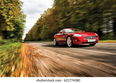 Vinnitsa, Ukraine - October 06, 2013. Red luxury Jaguar XK concept car -  on road in motion