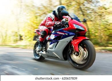 VINNITSA, UKRAINE - OCTOBER 3, 2012: Sexy biker man standing with red sport motorcycle Honda CBR Fireblade 1000RR