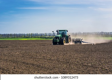 Vinnitsa/Ukraine - 04/23/2018: The tractor sows the seeds of agricultural crops in a dry land, leaving behind a pillar of dust