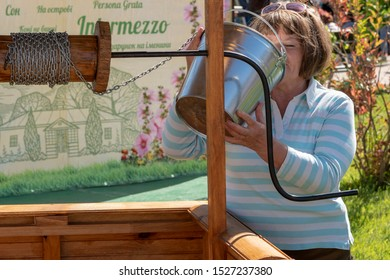 Vinnitsa.Ukraine 07.09.2019. Woman drinks water from a bucket. Iron bucket. bucket in the well. Water supply, water availability concept.
