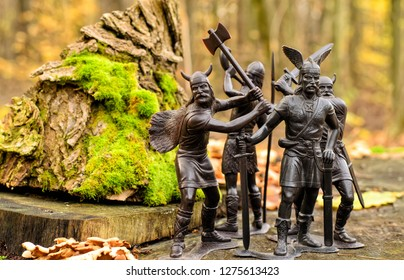 VINNYTSIA OBLAST, UKRAINE - OCTOBER 27, 2018: Group of four toy soldiers (Vikings), standing on a wooden surface beside a mossy piece of wood and ready to fight, epic Old Norse and Ragnarok themes