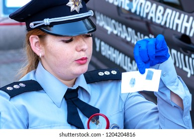 Vinnytsia, Ukraine. 22.09.2018. Woman policeman. The police expert with a magnifying glass and fingerprints. Concept biometric data of the person. Identification of the person on fingerprints.