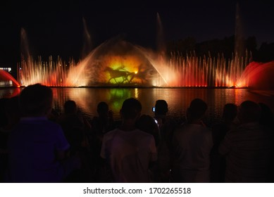 "VINNYTSIA, UKRAINE - AUGUST 07, 2015: People look to a fountain, illuminated by a projector near the ""Roshen"" plant in the center of Vinnytsia."