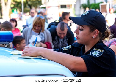 Vinnytsia,Ukraine.22.09.2018. The police officer writing ticket while standing by car. The law enforcement officer processes documents on offense. cop writes. Policeman writing fine bill for a driver